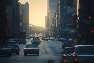 Walking around Lower Manhattan in the mid 1970s. Cars and stores on Canal Street illuminated by golden late afternoon light. Looking west to the the abandoned West Side Highway and the old Canal Street Bridge. New York. March 1975