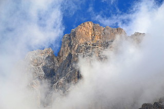 Clouds swirling around a Dolomites mountain wall