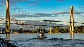 Tug passing under three bridges