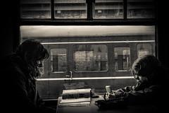 Distractions (neal1973) Tags: light transport travel carriage dark mono blackandwhite train child woman window reading phone