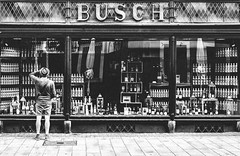 Liqueur Shop (ThorstenKoch) Tags: streetphotography street strasse stadt schatten silhouette shadow shopping liqueur shop monday macro blackwhite bnw city candit monochrome man düsseldorf duesseldorf thorstenkoch fuji fujifilm xt10 grain korn