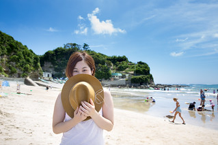 Young woman holding straw hat in beach
