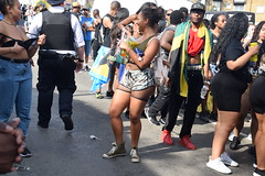 DSC_2791 Notting Hill Caribbean Carnival London Aug 28 2017 Police Constable and Girl Undressing in Black Bra (photographer695) Tags: notting hill caribbean carnival london exotic colourful costume dancing lady showgirl performer aug 28 2017 stunning ladies police constable girl undressing black bra