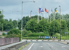 Flags Growing Well (M C Smith) Tags: arrows flags trees green sky blue clouds white railings pavement pentax k3ii lamps weeds bushes signs