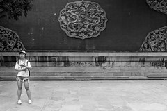 Alone with dragons (Go-tea 郭天) Tags: pékin beijingshi chine cn beijing forbidden city imperial palace ancient history historical historic culture traditional tradition wall fresco dragon candid portrait woman young tourist touristic listen listening cap audio guide stand standing alone lonely discover discovering old street urban outside outdoor people bw bnw black white blackwhite blackandwhite monochrome naturallight natural light asia asian china chinese canon eos 100d 24mm prime mobile phone cell celluluar cellphone bottle water plastic