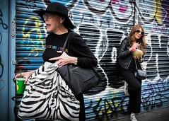 A Woman on the Edge (XBeauPhoto) Tags: graffiti london candid carrierbag portabelloroad shopper shopping shutters streetart streetphoto streetphotography stress urban woman