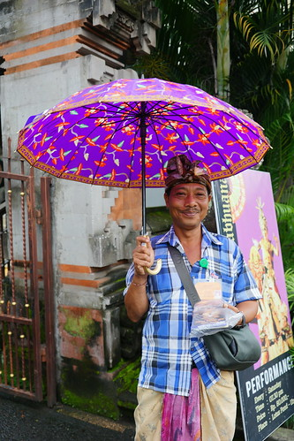 Man in pink parasol hands out brochures at the Ubud Water Palace
