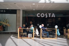 Costa - Chester (35mmFilmPhotography) Tags: costa coffee shop arcade mall light shadows people men women windows chairs tables lines buys shoppingarcade shoppingmall chester england uk travel travelling travller filmisnotdead ishootfilm filmisntdead filmrevival 35mm 35mmfilm photo photograph photography photographer negative scan analog analogphotography analogue candid casual capture rangefinder camera