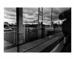 Convenience store, Superior, Wisconsin, out of business (Richard C. Johnson: AKA fishwrapcomix) Tags: leicaq leitz28mmsummiluxf17 blackandwhite bw monochrome street crosswalk signs automobiles paper outdoor economicdownturn thegreatrecession sunsetsinthewest civisromanussum spqr architecture reflections landscapeofdecline trees text clouds cigarettes tobacco car road superior wisconsin outofbusiness selfportrait shadow window storefront icamesofarforbeauty thecaptaininvites everyoneto joinhimon thepromenade deckandthe bandwillplay nearermy godtothee sictransitgloriamundi
