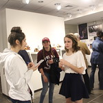 A student takes notes as a senior explains her capstone project at the gallery show.
