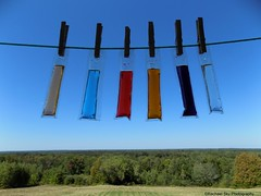 Hanging out the Freeze Pops (rachael242) Tags: freeze pops ice colors sky blue trees grass field bushes pegs wood wooden line clothes hang up out abstract fun food candy landscape orange purple red clear peach liquid melt melting