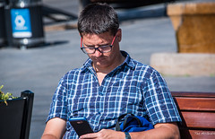 2017 - Montreal - People - 2 of 6 (Ted's photos - Returns Late November) Tags: 2017 canada cropped montreal nikon nikond750 nikonfx tedmcgrath tedsphotos vignetting montrealquebec quebec male man sitting seated glasses cellphone bokeh wristwatch shadow backpack frown