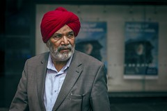 The Red Turban (Leanne Boulton) Tags: portrait urban street candid portraiture streetphotography candidstreetphotography candidportrait streetportrait streetlife closeup man male face facial expression look emotion feeling mood sikh turban religion faith suit stylish colourful tone texture detail depthoffield bokeh splittone orangeteal orange teal cinematic processing naturallight outdoor light shade shadow city scene human life living humanity society culture people canon canon5d 5dmarkiii 70mm character ef2470mmf28liiusm color colour glasgow scotland uk red