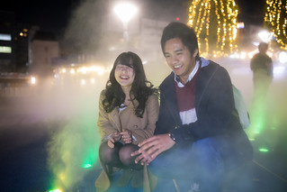 Happy high school couple playing in fog under Christmas lights