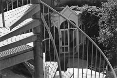 (frscspd) Tags: 51620019 20170419 pentax pentaxmx mx takumar takumar58mm 58mm ilford ilfordxp2 ilfordxp2400bw xp2 film filmgrain amsterdam hotel outofmywindow canal spiralstaircase spiral staircase fireregulations fireescape garden folly shed