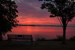 August Sunrise (Jolynn's Photography) Tags: summer sunrise waterfront water skies trees bench landscape