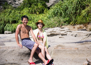 Young couple in swimwear sitting on rocks