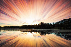 Seeleys Bay Explosion (Matt Molloy) Tags: mattmolloy timelapse photography timestack photostack movement motion colourful sky sunset sun light clouds trails lines radiant explosion trees boat water reflection deanslane seeleysbay ontario canada landscape nature lovelife