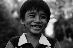 A Free Ride to Happiness (thirdworldsong) Tags: cambodia locals people childhood boy smile happiness thirdworld joy love exposure monochrome ngc blackandwhite nw portrait light youth outdoors natural unedited nofilter photography beautiful life bicycle culture ethnic minority human bw 35mm fujifilm streetphotography candid story portfolio artists travel wanderlust vagabond lost hope