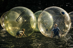 Women are from Venus, Men are from Mars (markfly1) Tags: kids playing fun children boy girl circular water walking zorbs orbs round men from mars women venus planets planetary blue yellow black white colour happy activity street candid