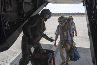 Marine helps members of the media onto an MV-22 Osprey.