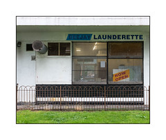 Council Estate Launderette, South London, England. (Joseph O'Malley64) Tags: launderette laundry councilestate concretestructure southlondon london england uk britain british greatbritain signs signage louvres vents ventilation ventilationfans flue pipes steelmesh windows security panelling accesscovers pavement steelfencing lawn weeds homes housingestate blocksofflats towers towerblocks highrise highrisehousing socialissues highdensityhousing urban urbanlandscape fujix x100t accuracyprecision
