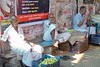 Underneath the posters, the bazaar, Ernakulam (Yekkes) Tags: lemons asia india kerala enrakulam market bazaar fruit people relaxing dhoti pondering bench