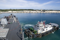 A harbor tug boat assists USS Sterett as the ship departs Naval Base Guam.