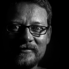 Introspective (Christian Hacker) Tags: selfportrait blackandwhite monochrome canon50d introspective myself beard glasses eyes staring head human depthoffield dof bw face happy male diy lightingrig christianhacker illumination illuminated shadow partial smile smiling spectacles specs iris