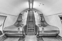 Escalator Six (Douguerreotype) Tags: urban monochrome underground tiles city bw uk metro escalator stairs england british blackandwhite mono subway architecture britain london symmetry gb metal steps tube tunnel