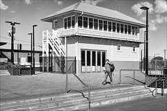 ringwood-8477-bw-ps-w (pw-pix) Tags: station trainstation railwaystation steps rails handrails planters plants tiles paved pavers poles lights person woman walking talking phone bag fence wires oldsignalbox restoredsignalbox sky clouds pt lilydaleline belgraveline ringwoodstation ringwoodrailwaystation maroondahhighway ringwood easternsuburbs melbourne victoria australia