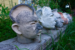 head council [Explored] (KevinIrvineChi) Tags: ceramics ceramic explored explore flickrexplore grasses grass bench glazed fired clay ridged faces ears eyes mouths noses profiles ny newyork hurley creations artworks artwork art linedup line outdoors outside mor morpipman creatures crearures heads head sculptures sculpture sony dscrx100