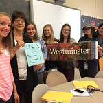 Students and faculty pose for a picture with a Westminster poster
