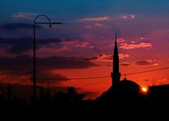 the sky over sarajevo (sarajevo, bosnia and herzegovina) (bloodybee) Tags: sarajevo bosniaandherzegovina formeryugoslavia europe street sunset sky clouds lamp lamppost streetlight mosque islam religion cable sun trip travel