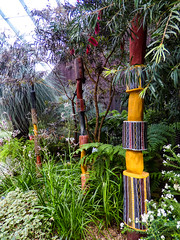 The Well Dressed Trees (Steve Taylor (Photography)) Tags: art sculpture carving yellow red brown green wood asia city singapore plant foliage flower african flowerdome gardensbythebay fern