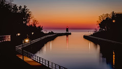 Sundown along the Pier (T P Mann Photography) Tags: dusk evening low exposure long michigan lamppost railing shadows orange sky color reflections water sea seascape lake river pier lighthouse light sunlit sundown sunset sun greatphotographers