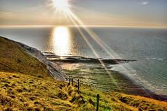 Rays of Light (Croydon Clicker) Tags: sunrays sunshine sunburst reflection sea ocean cliffs grass fence headland foreshore rocks sky haze sun nikon sigma 1000v40f