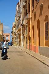 Trapani / Italy / Via Baracche / The motorcyclist (Pantchoa) Tags: trapani italie port méditerranée sicile rue photoderue streetshot façades architecture couleurs typiques ciel bleu jaunes nikon d7100 1685mm moto motocycliste véhicule perspective