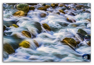 White silky water flowing downstream over the rocks and boulders