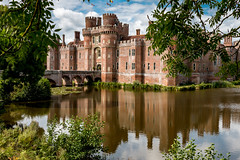 Moat and castle at Herstmonceux (Keith in Exeter) Tags: herstmonceux castle fortress moat gateway tower bridge arch window crenelation arrowloop chimney manorhouse flagpole flag water lake lily tree ash reflection sussex england english brick building architecture landscape explore chateau schloss moatedcastle castillo castello