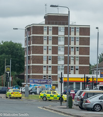 The Incident (M C Smith) Tags: pentax k3 flats petrolstation road pavement cars bluelights parking lamps signs yellow lines trees green sky blue clouds white railings