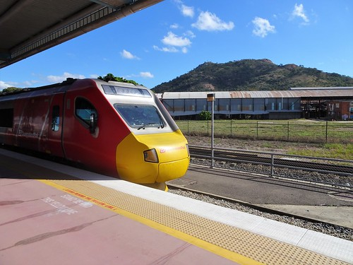 Townsville. The Spirit of Queensland train to Cairns beside the platform with Castle Hill in the background and some rusty old rail sheds.