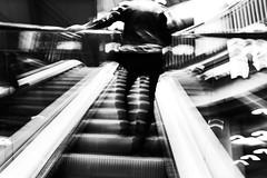 Shaking Things Up 7.365 (ewitsoe) Tags: fugifilm ewitsoe lookingtoexhibit mono blackandwhite synergy man escalator mall shopping browar stary poznan polska poland art motion energy energetic goingup down sideways fuji x100f film street urban