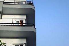 Day 259 : Is for ... The Third Floor Tenant (Storyteller.....) Tags: nikon nikon365 365 deep365 buliding balcomny windows man arm hand tenant gray black blue sky architecture city floor red
