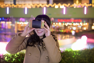 High school girl playing with VR glass under Christmas lights