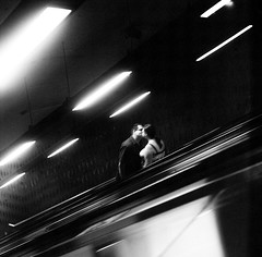 escalating (gguillaumee) Tags: film analog grain blur rolleiflex kodaktrix subway underground metro couple love lovers escalator kiss lights dark dramatic candid streetphotography street mtl montreal bw blackandwhite