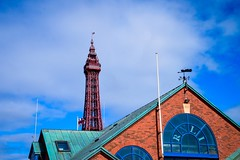 RNLI Station and the Tower. (rustyruth1959) Tags: nikon nikond3200 tamron16300mm alamy uk england lancashire blackpool blackpooltower rnli blackpoolrnli rnlistationblackpool rnlistation lifeboats lifeboatstation outdoor building roof architecture flag rnliflag unionflag structure tower windows sky bluesky weathervane lifeboatweathervane aerial 1998 dateplaque numbers letters arched archedwindow redbrick brickwork promenade centralpromenade blackpoollifeboats blue skylight viewingplatform shop visitorscentre angles