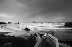 the persistent pull of the sea (manyfires) Tags: film analog nikonf100 35mm bw blackandwhite beach coast coastline shoreline shore sea ocean pacificocean pacificnorthwest pnw oregon bandon bandonbythesea tide waves moody stairs landscape seascape stormy