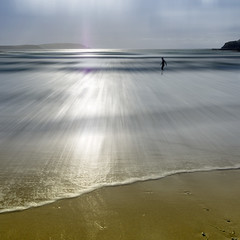 Stepping Out (Bruus UK) Tags: trevone beach cornwall seascape waves flare sunlight sun evening surf surfing solo alone tide sand coast summer dusk rocks backlight sky hazy reflection motion movement marine water