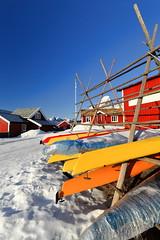 Kayaks-red cottages-rorbuer in Reine village. Helvetestinden-Stamprevtinden-Moltbaertinden-Breiflogtinden-Olstinden mounts background. Moskenesoya-Lofoten-Nordland-Norway. 0307 (rweisswald) Tags: kayak yellow orange fiberglasshull rowboat wood red cottage cabin hut rorbu rorbuer townhouse touristlodgement snow snowy snowcovered snowcappedmountain peak cold winter calm quiet stillness glazedwindow casementwindow closed doorframe windowframe board panel plank flagpole flagmast flagstaff gableroof sodroof turfroof greenroof helvetestinden stamprevtinden moltbaertinden breiflogtinden olstinden reine moskenes moskenesoya lofoten nordlandfylke norway